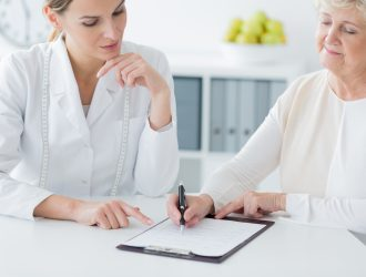 Elderly woman choosing a diet plan during an appointment at the dietician's office